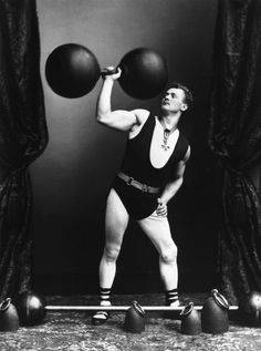 A strongman poses in 1895 in a women's bathing suit. | 20 Redonk Ways People Worked Out In The Olden Days