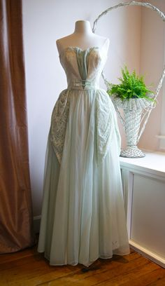 This gorgeous 1950s gown features a romantic and flowing floor-length skirt with a green tulle under layer, silky rayon lining, and a green chiffon