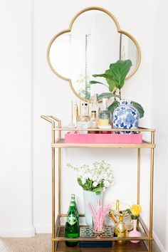 A Florida, Bright and Colorful Dining Room tour designed by Megan Martin Creative. White dining shelves, vintage colored goblets, pottery barn white dishware, tassel curtains, Lighting Connection Gold Linear Cage Pendant, gold flatware, colorful bar cart