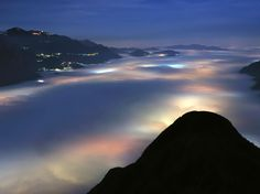 Blanket of clouds.. so cool!  Lago di Olginate, Italy  A layer of low clouds covers the alpine valleys of northern Italy, just south of Lake Como. The clouds are just dense enough to hide uniformly the valley and also filter the artificial lights below like they were an opaque blanket. Above the layer, moonlight and high cirrus clouds make the night less dark.