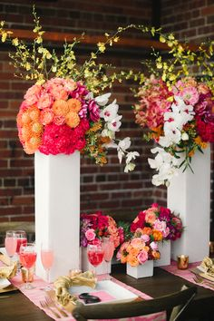 Orange and pink floral centerpieces in an urban to rustic setting.