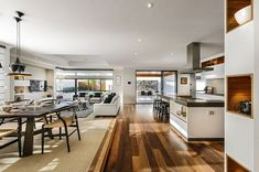 Open floor living area with the wishbone chairs and Tom Dixon lighting at the dining space