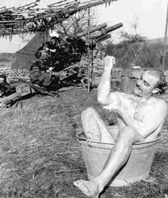 SPRING CLEAN-UP. An artilleryman takes time out for a bath during a warm spring afternoon while other members of the 105-mm. howitzer crew remain near their piece.