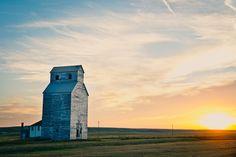 Tony Bynum sun sets behind an old grain elevator on the prairie of montana