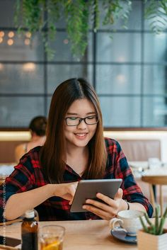 Smiling Asian Woman with Glasses Using Tablet Computer at the Cafe by Aleksandra Jankovic