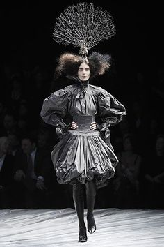 """Alexander McQueen """"I've got a 600-year-old elm tree in my garden and I made up this story of a girl who lives in it and comes out of the darkness to meet a prince and become a queen."""" What emerged was a darkly gothic creature with huge backcombed hair, wearing head-to-toe shrink-wrapped black leather with a skeletal branch as her crown. #alexandermcqueen2008"""