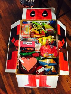 Deadpool care package. My husband is obsessed with deadpool so I made a deadpool themed care package. On top of that I added cute quotes on the inside along with pics of the family. Also a deck of cards with 52 reasons why I love him, a usb filled with photos of the family, a hard drive full of movies and TV shows his favorite munchies and a ton of other stuff. He absolutely loved it!