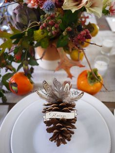"""Pine Cone Wedding Place Card: Got a soft spot for childhood art projects? This pine cone place card holder with """"turkey"""" feathers is an elevated version of an elementary school creation. Great for a sense of whimsy and a chuckle, or on a kids' table for a fall wedding reception."""