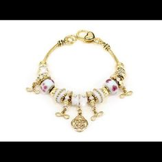 """White enamel and clear crystal infinity bracelet. White enamel accented in hand painted designer flowers and clear crystals adorn this designer infinity bracelet.  The charms, 3/8"""" to 1/2"""", slide along the gorgeous gold bracelet.  The bracelet is finished with an exquisite lobster claw  closing.  Everything about this bracelet screams quality. Jewelry Bracelets"""