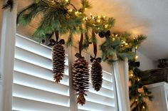 Greenery, pinecones and mini lights for an above the window decoration.