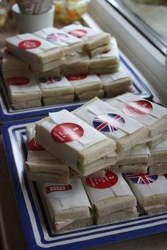 Keep your finger sandwiches in order by wrapping them in grease proof paper and sealing with a British sticker.  [Photo: Pinterest]
