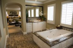 This large rectangular tub sits on white wood marble topped enclosure over tile flooring with matching brown tone. Arch doorway on left leads directly into master bedroom.