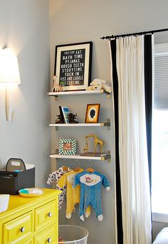 I like the shelving on this wall - particularly the cute outfits hanging. Could be used for super hero costumes when he gets older