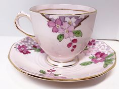 Delightful, soft pink envelopes this lovely floral tea cup and saucer. This tea cup and saucer by Tuscan Bone China of England is detailed with an aristocratic handle, footed cup and hand painted rose border. Tuscan has been producing since 1898. It was one of the best companies.
