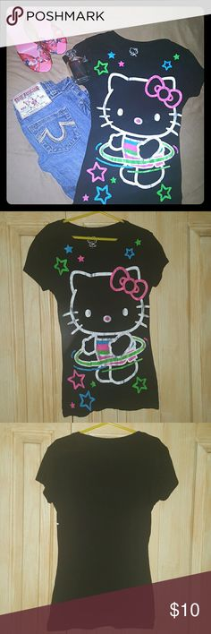 Hello Kitty Hula Hoop Tee Adorable HK black crewneck tee featuring Hello Kitty hula hooping and neon stars all around her. This is a juniors tee shirt! Fits women's size s, maybe medium, as long as your chest isn't too big (like mine now.) I only wore it once. Now I would be stretching it out across the bust way too much so it needs a new home. Perfect condition, not a loose string or stain anywhere. I have other HK and junior sizes to bundle and save $! Sanrio Tops Tees - Short Sleeve