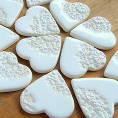 Podziękowania ślubne dla gości  Zestaw 70 magnesów ceramicznych w postaci przepięknych szkliwionych serduszek w kolorze białym przyozdobionych motywem koronki. Każde serduszko leży na gniazdku sianka w papierowej torebce przyozdobionej czerwonym lub niebieskim serduszkiem i zamkniętej na małą drewnianą klamerkę (przy zakupie proszę i informację dotyczącą koloru serduszka na torebce).  Dostępne w butiku Madame Allure!