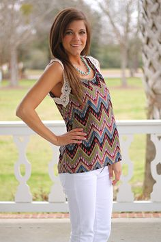"""Chevron alert! The colors in this top are gorgeous and we love the variety of geometric shapes within the chevron pattern. Plus, how cute is the ivory lace around the arms?! Miranda slipped hers on with white skinnies for a fabulous look!   Fits true to size. Miranda is wearing a small.  from shoulder to hem:  small=24.5""""  medium=25  large=25.5"""
