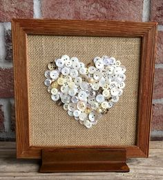 A pretty collection of white, cream and tan small buttons make a heart shape on tan burlap in a rustic wood frame. It has a rustic, industrial