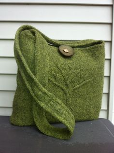 """A beautiful, cabled tree serenely stands guard on the front of this lightly felted bag. It's roughly 13.5""""X12"""", just the right size for everything you need on the go. You can choose between an I-cord handle (as shown) or a simpler, flat handle. The sample is knit using 4 skeins of Wool of the Andes Worsted Yarn in the gorgeous Rooibos Heather. The closure is the Antler 2"""" Toggle. It requires intermediate skills including cabling, knitting in the round and felting."""
