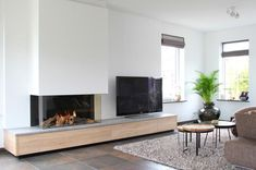 Modern built-in fireplace with gray stone top and custom-made drawers with . Modern built-in fireplace with gray stone top and custom-made drawers with a wooden front Professio Living Room Decor Fireplace, Fireplace Tv Wall, Wooden Fireplace, Living Room Tv, Fireplace Design, Custom Fireplace, Fireplace Modern, Fireplace Garden, Living Room Designs