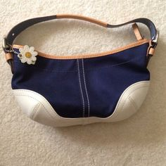 Authentic Coach Navy Daisy Purse Authentic Coach Purse in navy canvas-like fabric with white leather accents and daisy charm. It was a limited edition! Only used once or twice; like new condition. The only mark is a tiny half centimeter mark on the very bottom of the bag (pictured) but not visible when using. One zippered pocket inside. Comes with dust bag. Coach Bags
