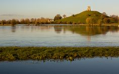 The winter suns rises over flood water still lingering in fields on the Somerset Levels below Burrow Mump and the ruins of St Michael's church in Burrowbridge