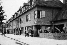 Gezicht op de voorgevels van de winkelwoonhuizen Amsterdamsestraatweg 560 (rechts)- lager te Zuilen; in het midden, in zwart pak, G.H. Koenders. ca1934