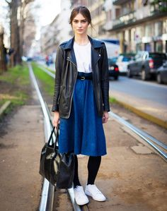 Black leather jacket, white t-shirt tucked into a denim midi skirt and white sneakers