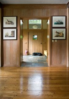 The home's new entry is spacious and light-filled. The wood-paneled walls give the space a rustic aesthetic. Designed by Bruce Abrahamson, AIA. Photo by Andrea Rugg.