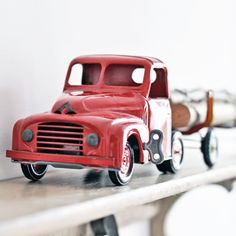 A vintage French metal toy truck. It's a bright, pretty red and still has the original wind-up key.