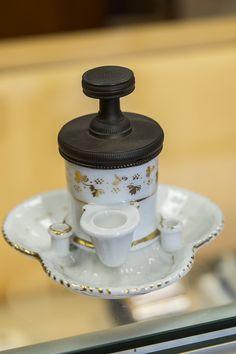 Antique French porcelain body inkwell with brass lid. Marked on top Encrier Pompe Bocquet Brevete Medaille D'Arget 1839. Features hydraulic design with small basin and two quill holders. Missing basin
