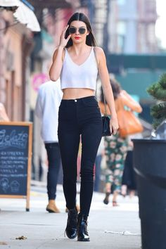 Kendall Jenner proves black-and-white is always right—especially with the added touch of a classic red lip. The model made her way through Manhattan's streets in a chic, white crop top and black skinny jeans with Louis Vuitton boots and a crimson pout.