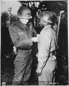 General Patton pins a Silver Star on Private Ernest A. Jenkins of NYC, NY a soldier under his command, October 1944.