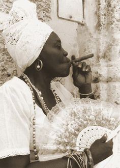 Best aware of the Vodun Queen who has a fan in one hand, and a smoking cigar in the other..