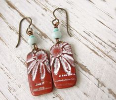 Polymer Clay Earrings featuring Tropical Dark Red Lacy Flower Design- Perfect for summer or when you need a pick-me-up, these tropical polymer clay earrings add a bit of whimsy to your wardrobe. The dark red/copper-colored clay tile has been impressed with a pretty, lacy flower stamp, then highlighted with white acrylic paint, sanded and buffed to a soft shine. The base and back are dark red/copper. The tiles dangle from hypoallergenic copper ear wire with small blue wood beads.