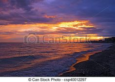 The purple and orange colors of a sunset are reflected in the waves.