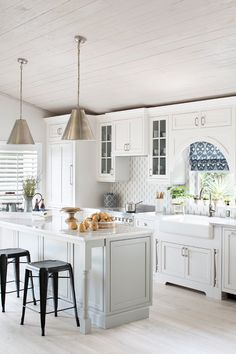 Pale Grey Island. Kitchen with white perimeter cabinets, pale grey island and…