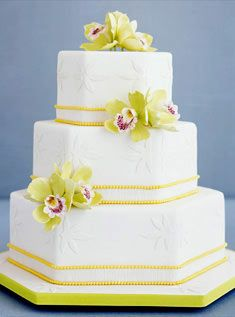 This three-tiered white hexagonal cake features raised floral appliques, a yellow-pearl trim, and sugar-paste green cymbidium orchids.      Photo By: Andrew McCaul