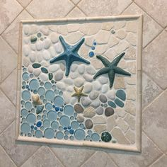 """18"""" x 18"""" Mosaic mural 'As The Tide Goes Out' with some funky glaze colors! This mural can be found on our website. In this particular bathroom shower installation it's framed with a travertine pencil liner trim. This mural is made with glass, stone, and various ceramic pieces such as starfish, shells, and more. Our murals are made with extremely durable stoneware clay and are suitable for any surface, whether it be indoor or outdoor. #wetdogtile"""