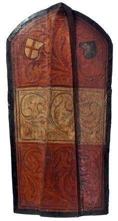 Pavois du type de Klausen. La structure date peut-être du XVe siècle. La face peinte représente les armes autrichiennes enrichi de rinceaux. Il se trouve en haut, à droite les armes de la Ligue de St Georges, à gauche un blason non identifié, une étoile sur un fond noir. Ce type de schéma est lié au duc Sigismond de Tyrol (1427-1496) et la Ligue Souabe. De nombreux pavois furent découvert en 1871 à Klausen. Et ils furent souvent repeint. H : 118 cm L : 60,5 cm. collection privée.