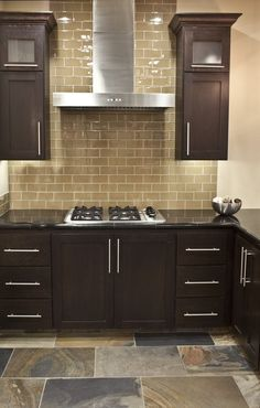 I like the color of this glass subway tile backsplash with the dark cabinets