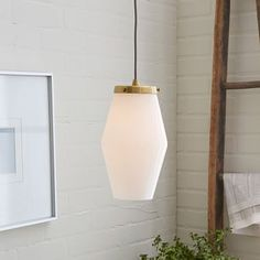 "6.5""diam. x 15""h. Glass Pendant - Single Mood lighting. The opal white shade and brass finished hardware of the Mid-Century Glass Pendant give it a cool, retro look, while its adjustable cord height makes it a great fit above a kitchen island or in an entryway.   6.5""diam. x 15""h. Adjustable hanging height. Metal frame in plated Antique Brass finish. Opal glass pendant in White. Gray cloth-wrapped cord. Hardwired."