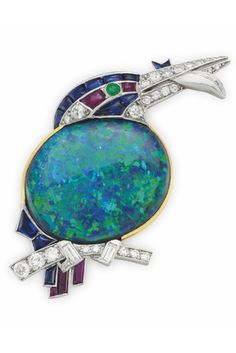 CARTIER - A LATE ART DECO BLACK OPAL, MULTI-GEM AND DIAMOND 'KINGFISHER WITH FISH' BROOCH, CIRCA 1939. Designed as a kingfisher bird perched on a circular-cut diamond branch, with a black opal body, calibré-cut ruby, sapphire and diamond-set head with cabochon emerald eye, mounted in platinum and gold, signed Cartier, London, numbered.