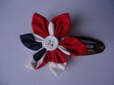 Barrette Cocorico Clic-Clac  Jolie barrette en coton rouge avec des ronds blanc et bleu, en forme de fleur, avec un coeur en bouton blanc. La barrette est une pince clic-clac argentée de 5 cm.