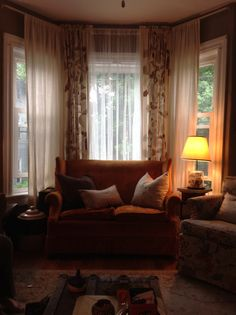 """DIY recycled Living room: Bay window dressed with ikea curtains and donated and found furniture. Curtains are hung from the cheapie white metal rods, about 3"""" from the 8' ceiling."""