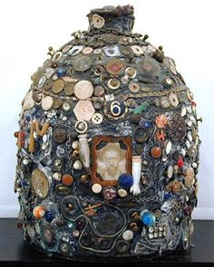 The first memory jugs were made by African Americans for grave adornments. Memory jugs are mosaic vessels covered in mortar and encrusted with pictures, shards, shells, and various personal and found objects. They were popular in Victorian times as folk La Danse Macabre, Post Mortem, Art Brut, Found Object Art, Altered Bottles, Arte Popular, Assemblage Art, Outsider Art, Mosaic Art