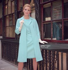 Ice blue shift dress worn with a loose-fitting coat and long white gloves.