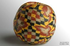 Checkerboard mosaic bead, Roman period   Period: Dating:30 BC–400 BC Origin:Egypt, Material:Glass (all types) Physical:1.5cm. (.6 in.) - 5 g. (.2 oz.) Catalog:GLS.VS.01007   This spherical checkerboard bead was made without a base bead. The whole bead is a slice of mosaic rod wrapped around a mandrel and shaped into a ball. It offers alternating checkerboard patterns separated by a black line: one is yellow, red, and white; the other is white, red, and yellow. The original pattern from…