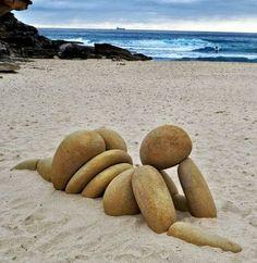 mujer en la playa hecha con piedras