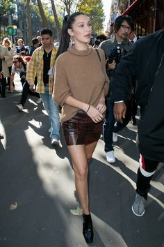 Bella Hadid throwing a cozy sweater over her tight skirt and completing the look with leather boots.